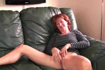 Рыжая зрелая дамочка ласкает пизденку на диванчике